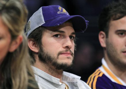 Actor Ashton Kutcher wears a worn Lakers cap as he sits courtside watching the Los Angeles Lakers play the Oklahoma City Thunder during Game