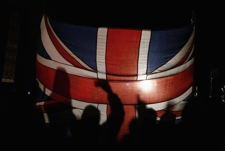 Falkland islanders are silhouetted behind the Union Jack as they react after hearing the results of the referendum in Stanley March 11, 2013