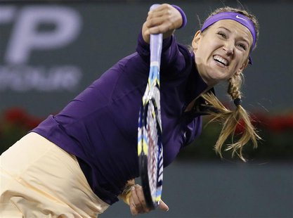 Victoria Azarenka of Belarus serves against Kirsten Flipkens of Belgium during their match at the BNP Paribas Open WTA tennis tournament in
