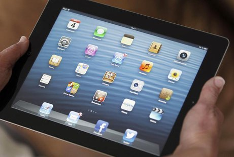 An illustration picture shows application icons on an Apple Ipad tablet held by a woman in Bordeaux, Southwestern France, February 4, 2013.
