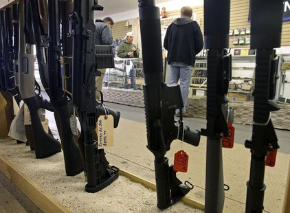 Customers are seen shopping for handguns through a rack of assault rifles at the Guns-R-Us gun shop in Phoenix, Arizona, December 20, 2012.