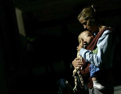 A nursing mother holds her son in front of the Delta airlines counter during a protest at Fort Lauderdale airport, Florida November 21, 2006