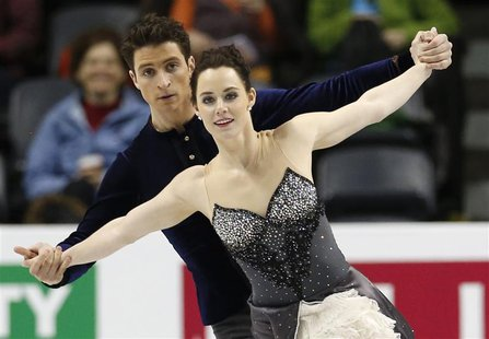 Ice dancers Tessa Virtue (R) and Scott Moir of Canada skate during practice sessions at the ISU World Figure Skating Championships in London