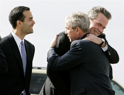 U.S. President George W. Bush (C) hugs his brother, former Florida Gov. Jeb Bush (R), while Jeb's son George P. Bush (L) smiles after arrivi