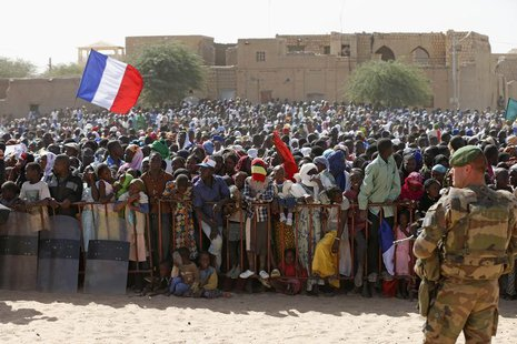 A French flag is seen as people gather to greet French President Francois Hollande during his two-hour-long visit to Timbuktu February 2, 20