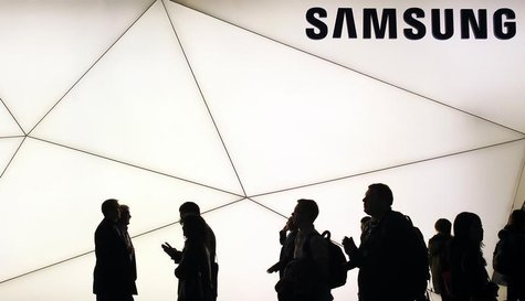 People walk past a Samsung stand at the Mobile World Congress in Barcelona February 25, 2013. REUTERS/Albert Gea