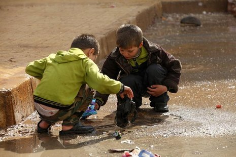Children remove trash blocking the drains in the Al Inzarat district in Aleppo February 17, 2013. REUTERS/Hamid Khatib