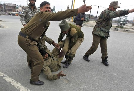 Indian paramilitary soldiers gesture as their injured colleague lie on the ground during a gunfight in Srinagar March 13, 2013. Two militant