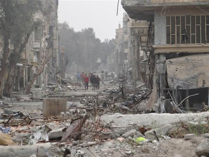 People walk on a street lined with buildings damaged by what activists said were missiles fired by a Syrian Air Force fighter jet loyal to P