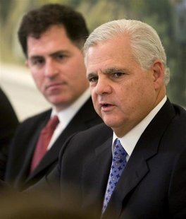 EMC Chief Executive Joe Tucci (R) speaks at a news briefing to release two reports addressing the impact of information technology on the en