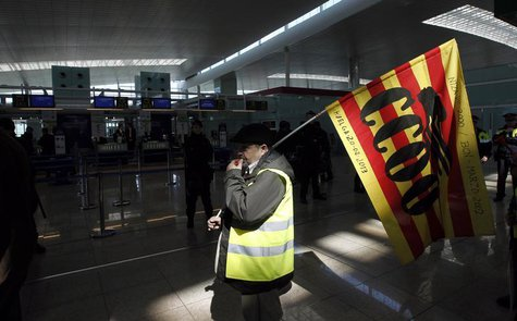 A man holding a Comisiones Obreras (CCOO) trade union flag walks past Iberia's check-in desk during an Iberia workers strike at Terminal 1 o