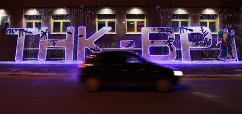 A car drives past an illuminated sign displayed in front of the local office of TNK-BP company in the Siberian city of Tyumen, January 17, 2