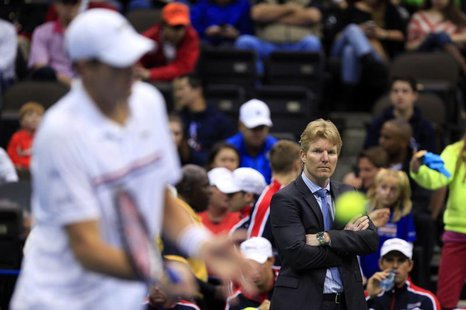 U.S. team captain Jim Courier (R) watches as John Isner practises before his match against Brazil's Thomaz Bellucci during the Davis Cup wor