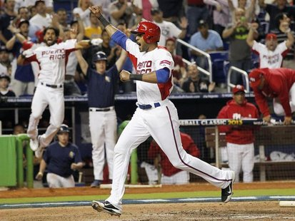 Puerto Rico's Alex Rios crosses the plate to scoring the go-ahead run in the eighth inning against Italy in a 2013 World Baseball Classic ga
