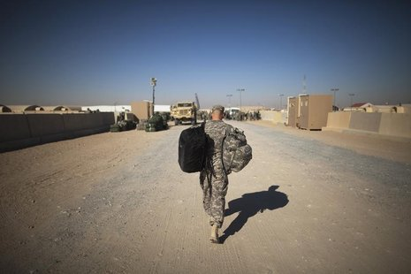 A soldier carries his bag to begin his trip back to the United States at Camp Virginia, Kuwait December 20, 2011. REUTERS/Lucas Jackson