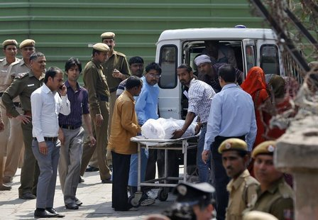 Hospital staff and relatives load the body of Ram Singh, the driver of the bus in which a young woman was gang-raped and fatally injured thr