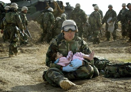 U.S. Navy Hospital Corpsman HM1 Richard Barnett, assigned to the 1st Marine Division, holds an Iraqi child in central Iraq in this March 29,