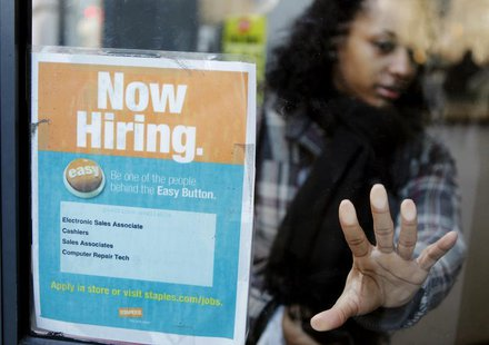 "A woman opens a glass door with a ""Now Hiring"" sign on it as she enters a Staples store in New York March 3, 2011. REUTERS/Lucas Jackson"