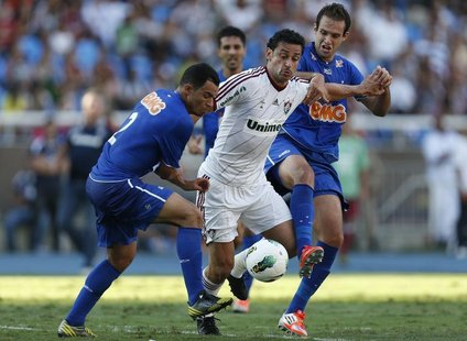 Fred of Fluminense (C) challenges Ceara (L) and Thiago Carvalho of Cruzeiro during a Brazilian Series A Championship match in Rio de Janeiro