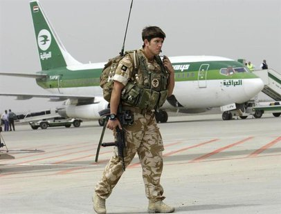 A British soldier walks on the tarmac near an Iraqi Airways Boeing 737 plane, during the handover ceremony of Basra's international airport
