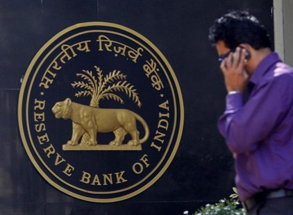 A man makes a phone call while standing near a Reserve Bank of India (RBI) crest at the RBI headquarters in Mumbai January 29, 2013. REUTERS