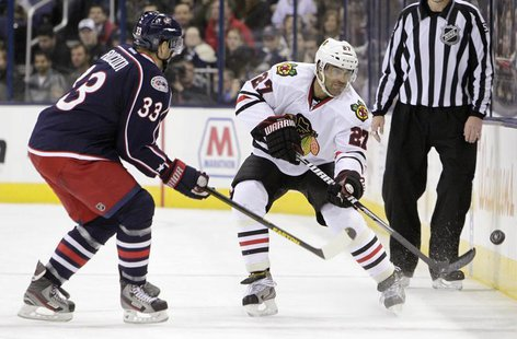 Chicago Blackhawks' Johnny Oduya (27) clears the puck as Columbus Blue Jackets' Adrian Aucoin (33) defends during their NHL hockey game in C