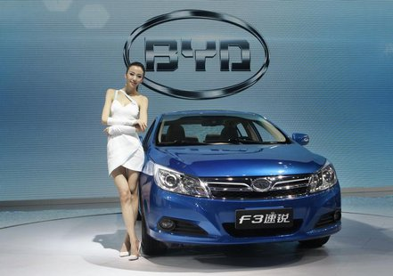 A model stands next to China's BYD F3 at Auto China 2012 in Beijing April 24, 2012. REUTERS/Jason Lee