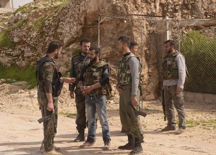 Soldiers loyal to Syria's President Bashar al-Assad talk as they hold their weapons in Khan al-Assal area, near Aleppo city March 12, 2013.