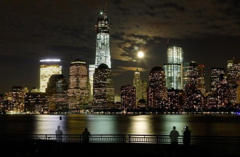 The moon rises behind the skyline of New York's Lower Manhattan and One World Trade Center as people stand along the Hudson River in Jersey