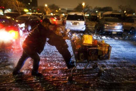 A child hangs on to shopping cart as his father pushes as they make their way to their car during a winter storm at Jersey City in New Jerse