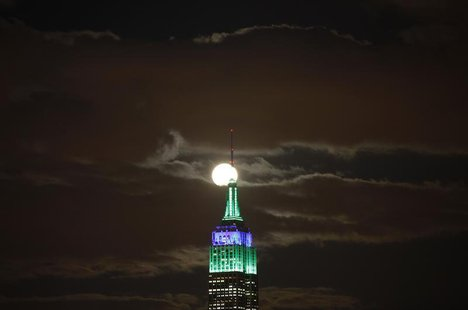 A full moon rises behind the Empire State Building in New York as seen from a park along the Hudson River in Hoboken, New Jersey, February 2