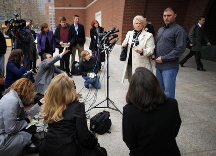 "Patricia Donahue and her son Michael, wife and son of a suspected victim under James ""Whitey"" Bulger, talk to reporters outside the federal"