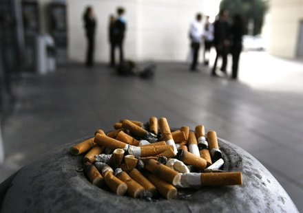 Office workers smoke on the pavement of their office in Nice, southeastern France, October 19, 2006. REUTERS/Eric Gaillard