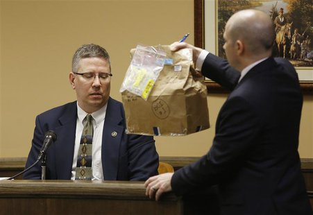 Prosecuting attorney Brian Deckert holds up a bag containing a blanket which was tested for genetic material in front of witness and Bureau
