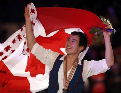 Patrick Chan of Canada carries his country's flag as he celebrates his gold medal finish after the presentation ceremony at the ISU World Fi