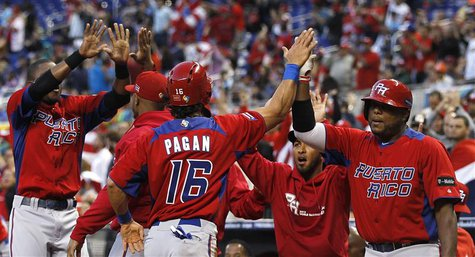 Puerto Rico's Angel Pagan (C) high fives with teammates after scoring the run driven in by Mike Aviles in the first inning of their 2013 Wor