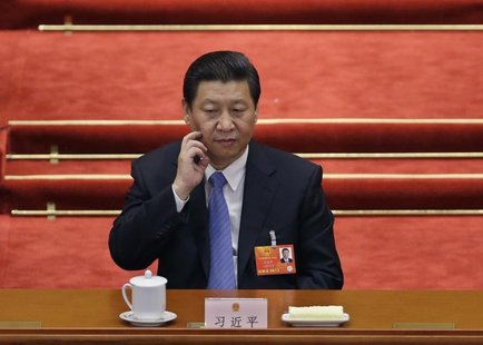 China's newly-elected President Xi Jinping scratches his face during the sixth plenary meeting of the National People's Congress (NPC) at th