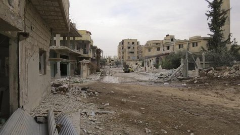 A view shows damaged buildings and a vehicle on a deserted street in Deraa February 22, 2013. Picture taken February 22, 2013. REUTERS/Ali A