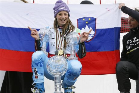Slovenia's Tina Maze poses with her women's overall, Giant Slalom and Super-G World Cup trophies at the Alpine Skiing World Cup finals in Le