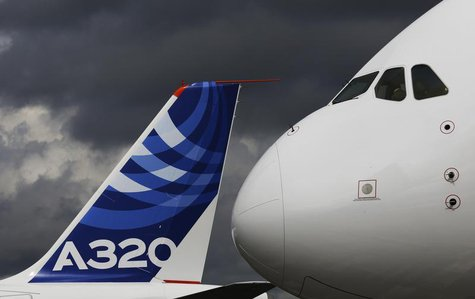 The nose cone of an Airbus A380 overlooks the tail fin of an Airbus A320 at the Farnborough Airshow 2012 in southern England July 10, 2012.