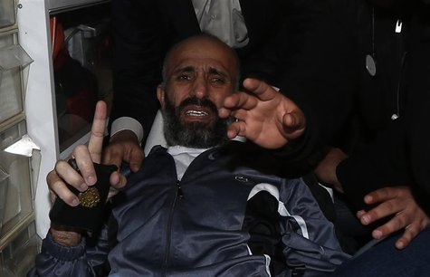 Freed Palestinian prisoner Ayman Sharawneh gestures as he holds a copy of the Koran inside an ambulance upon his arrival near Erez crossing