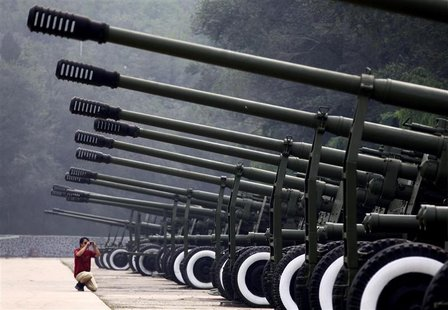 A visitor to the China Aviation Museum, located on the outskirts of Beijing, takes a photograph of a row of old anti-aircraft guns on displa