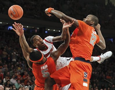 Louisville Cardinals guard Kevin Ware tries to pass the ball under pressure from Syracuse Orange forward C.J. Fair (5) and center Baye Keita