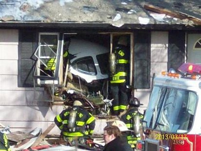 Firefighters and rescue workers look over the scene in South Bend, Indiana in this March 17, 2013 photo courtesy WNDU-TV after a small twin-