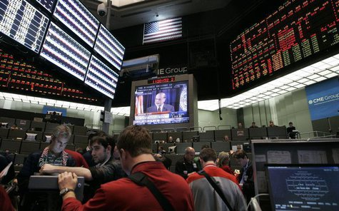 Traders at the CME Group watch a television broadcast of Federal Reserve Chairman Ben Bernanke as he answers questions during a first-ever n