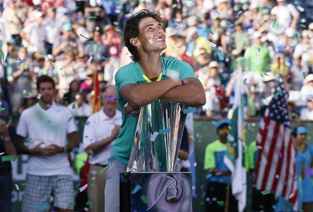 Rafael Nadal of Spain smiles as he leans on his trophy, while confetti flutters in the air, after he defeated Juan Martin Del Potro (rear L)