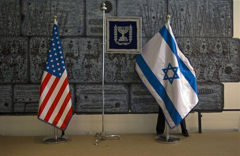 An employee arranges an Israeli national flag next to a U.S. one at the residence of Israel's President Shimon Peres in Jerusalem, ahead of