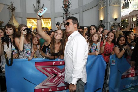 "Judge Simon Cowell poses with a fan at the season two premiere of the television series ""The X Factor"" at Grauman's Chinese theatre in Holly"