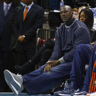 Charlotte Bobcats owner Michael Jordan watches as his team plays against the Chicago Bulls during the first half of their NBA basketball gam