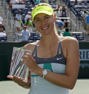 Maria Sharapova of Russia poses with a smaller replica trophy after defeating Caroline Wozniacki of Denmark in their women's singles final m